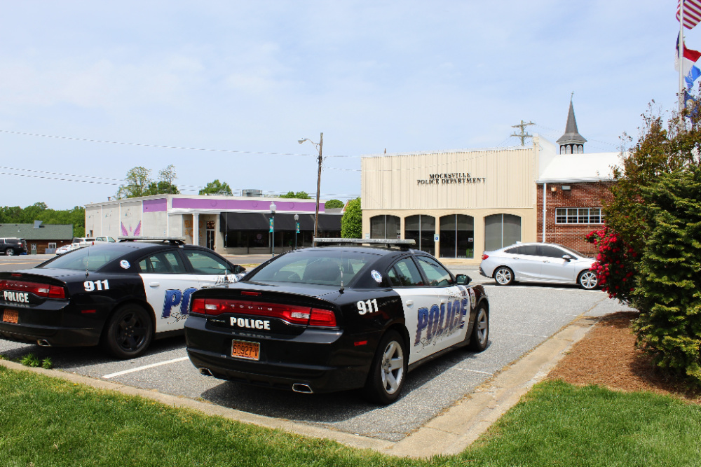 Putside image of the Mocksville Police Department Building and police cars